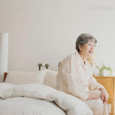 ベッドに座り微笑むシニア女性の写真素材 [FYI01948811]