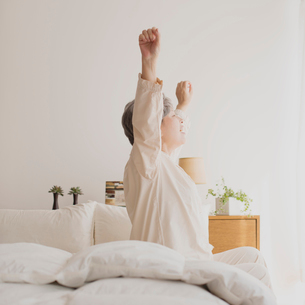 ベッドで伸びをするシニア女性の写真素材 [FYI01948813]