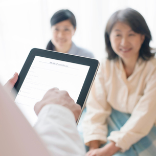 タブレットPCを持つ医者の手元(訪問医療)の写真素材 [FYI01948823]