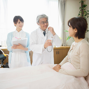 患者の診察をする医者と看護師(訪問医療)の写真素材 [FYI01948921]