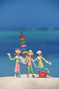 旅行中に地図を持って浜辺に並ぶ女性たちと道しるべ クラフトの写真素材 [FYI01949005]