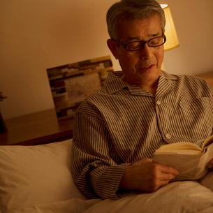 ベッドで本を読むシニア男性の写真素材 [FYI01949180]