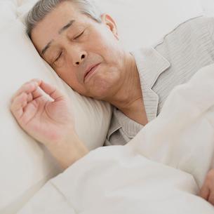 ベッドで眠るシニア男性の写真素材 [FYI01949195]