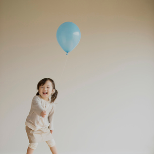 風船を持ち微笑む女の子の写真素材 [FYI01949629]