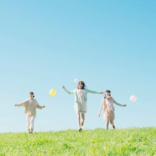 風船を持ち草原を走る3人の女性の写真素材 [FYI01949669]