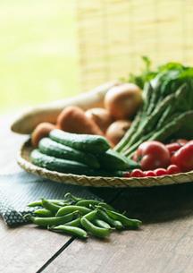 田舎のちゃぶ台の上にあるザルに盛った採れたて野菜の写真素材 [FYI01949858]