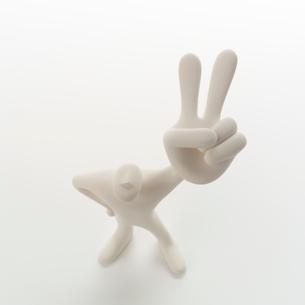 左手のピースサインを挙げて立つ人のオブジェ クラフトの写真素材 [FYI01949955]
