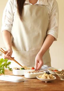 お弁当を作るエプロン姿の女性の手元の写真素材 [FYI01950030]