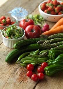 テーブルの上の採れたて野菜とサラダと野花の写真素材 [FYI01950340]