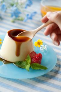 野花を飾ったプリンをスプーンですくう手元の写真素材 [FYI01950453]