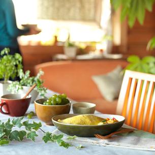 食事を運ぶ女性とテーブルの上に置かれたランチと観葉植物の写真素材 [FYI01950471]