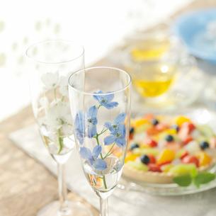 グラスに飾った花とフルーツタルトの写真素材 [FYI01950522]