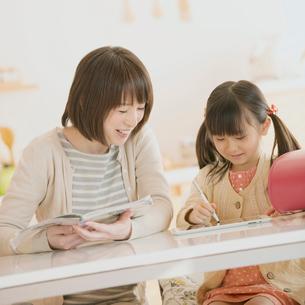 タブレットPCで勉強をする親子の写真素材 [FYI01950543]