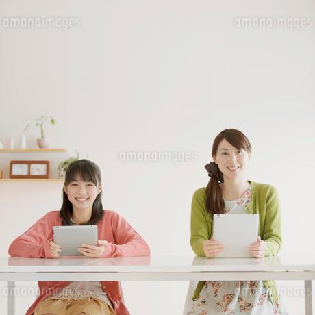 タブレットPCを持ち微笑む親子の写真素材 [FYI01950631]
