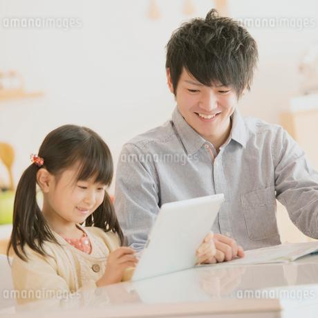 タブレットPCで勉強をする親子の写真素材 [FYI01950665]