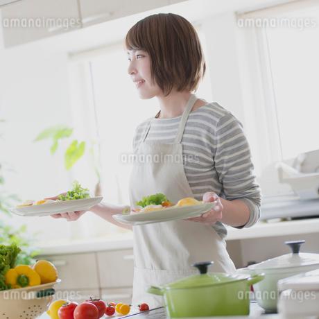 キッチンで料理を持ち微笑む女性の写真素材 [FYI01950715]