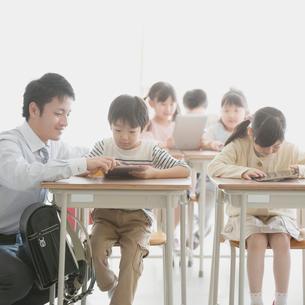 タブレットPCで勉強をする小学生と先生の写真素材 [FYI01950722]
