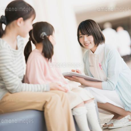 病院の待合室で順番を待つ親子と問診をする看護師の写真素材 [FYI01950738]