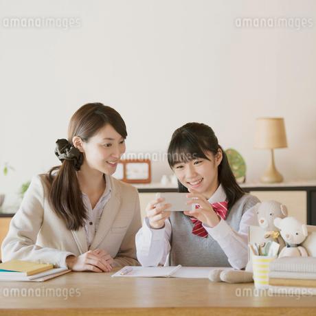 スマートフォンで勉強をする中学生と家庭教師の写真素材 [FYI01950741]