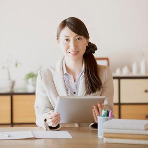 タブレットPCを持ち微笑む女性の写真素材 [FYI01950780]