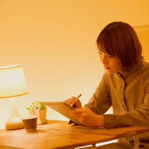 タブレットPCで通信講座の勉強をする女性の写真素材 [FYI01950820]