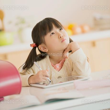 頬杖をつき考え事をする女の子の写真素材 [FYI01950836]