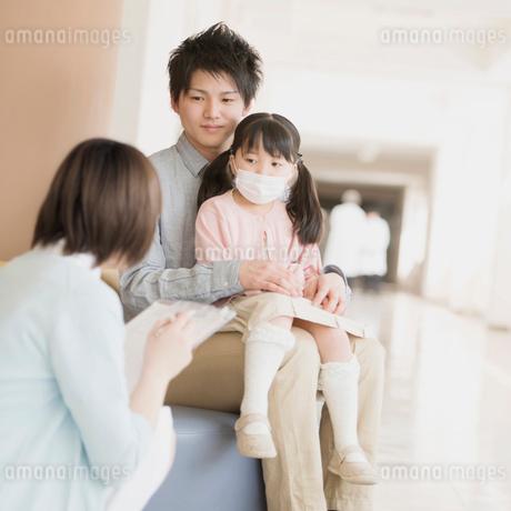 病院の待合室で順番を待つ親子と問診をする看護師の写真素材 [FYI01950840]