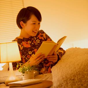 ベッドで本を読む女性の写真素材 [FYI01950853]