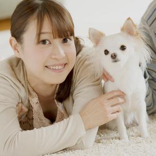 部屋でくつろぐ女性と犬の写真素材 [FYI01950861]