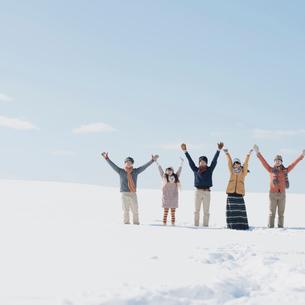 雪原で両手を挙げる若者たちの写真素材 [FYI01950869]