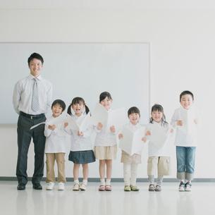 楽譜を持ち微笑む小学生と先生の写真素材 [FYI01950885]