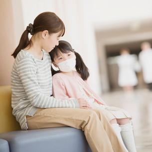 病院の待合室で順番を待つ親子の写真素材 [FYI01950886]