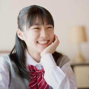 頬杖をつき微笑む中学生の写真素材 [FYI01950894]