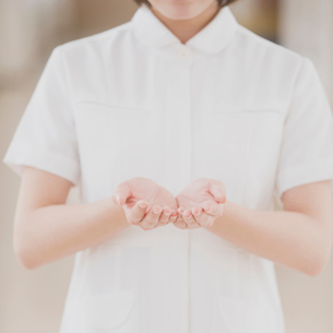 包み込むポーズをする看護師の手元の写真素材 [FYI01950900]