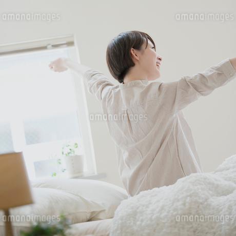 ベッドで伸びをする女性の写真素材 [FYI01950986]