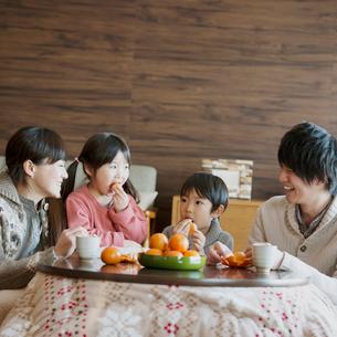 こたつでみかんを食べる家族の写真素材 [FYI01951007]