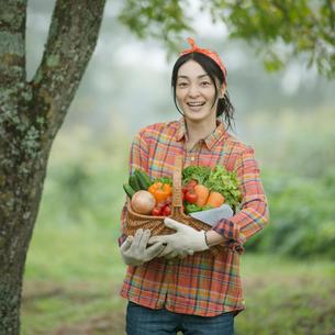 農園で野菜を持ち微笑む女性の写真素材 [FYI01951020]