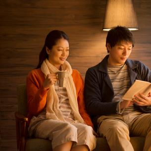 ソファーに座りくつろぐミドル夫婦の写真素材 [FYI01951058]
