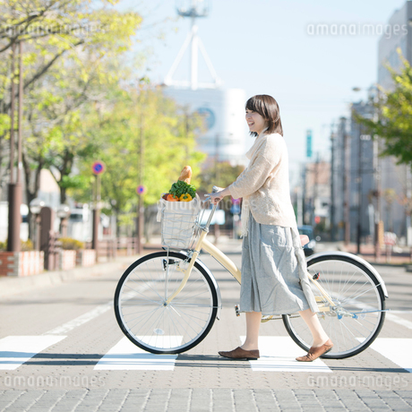 自転車で買い物をする女性の写真素材 [FYI01951075]
