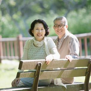 ベンチに座り微笑むシニア夫婦の写真素材 [FYI01951130]