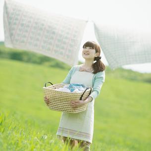 洗濯物を持ち微笑む女性の写真素材 [FYI01951135]