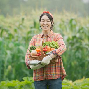 農園で野菜を持ち微笑む女性の写真素材 [FYI01951138]