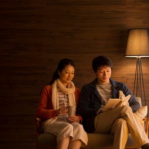 ソファーに座りくつろぐミドル夫婦の写真素材 [FYI01951160]