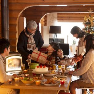 祖父母からクリスマスプレゼントをもらう孫の写真素材 [FYI01951200]