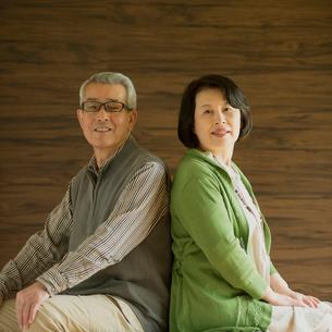 背中合わせに座るシニア夫婦の写真素材 [FYI01951221]