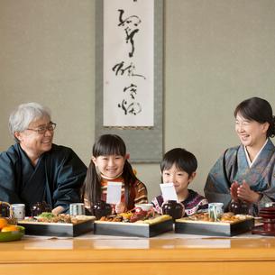 お年玉を持ち微笑む孫と祖父母の写真素材 [FYI01951244]