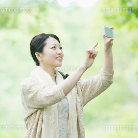 スマートフォンで写真を撮るミドル女性の写真素材 [FYI01951289]