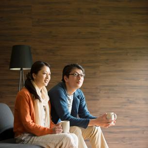 ソファーに座りくつろぐミドル夫婦の写真素材 [FYI01951290]