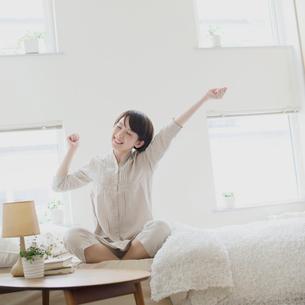 ベッドで伸びをする女性の写真素材 [FYI01951328]