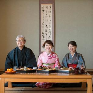 テーブルの上に並ぶおせち料理と微笑む家族の写真素材 [FYI01951336]